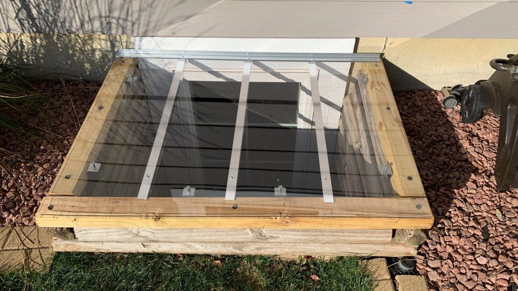 custom window well cover on window well made of wood